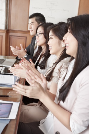 thier: A group business people clapping thier hand while on meeting in the office