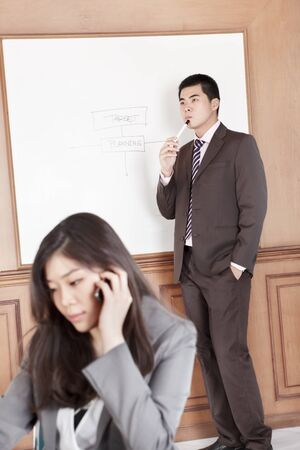 Chinese businesswoman on the phone while businessman preparing presentation on background photo