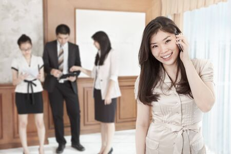 Chinese businesswoman is on the phone in the office photo