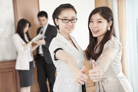 thumbs up group: Two businesswomen with their thumbs up in the offcei