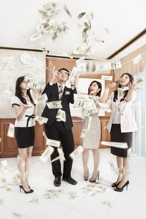 profit celebration: Group of business people happily looking at the thrown dollar bills in the office Stock Photo