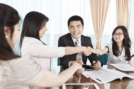 Group of business people handshaking to each other in the ofice photo