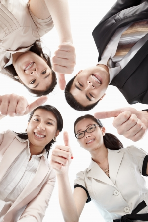Four business people looking to camera from low angle with thumb up