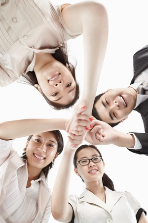 asian business women: Four business people looking to camera from low angle handshaking