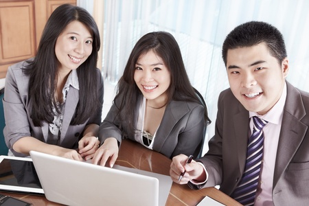 asian businessman: Group of Chinese business people smiling to camera in the office