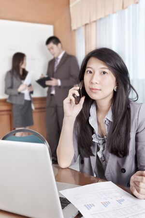 Chinese businesswoman talking on cell phone in the office photo