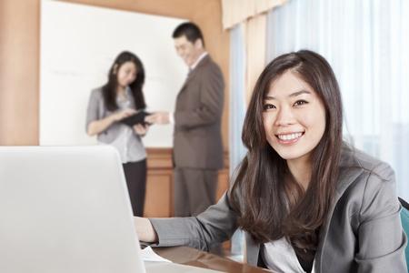 laptop asian: Empresaria china sonriendo a la c�mara en la oficina Foto de archivo