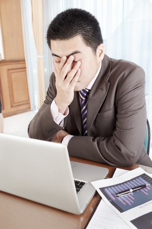 tired businessman: Chinese businessman working in office