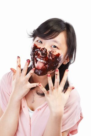finger licking: Chinese female with her face spread with chocolate cream, isolated on white background Stock Photo