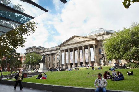 victoria park: Melbourne, Australia - April 11th, 21012 : Victoria State Library with lots of people sitting on the grass in front of it