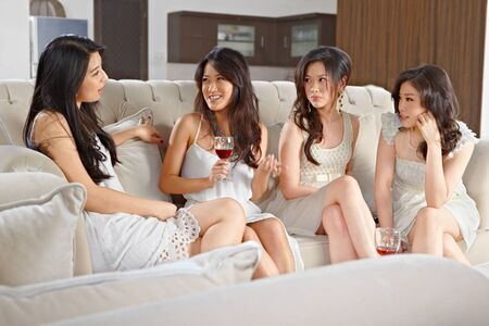 Four young beautiful women meeting at home photo