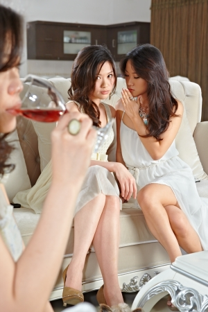 envy: Girls gossiping about their friend on the meeting