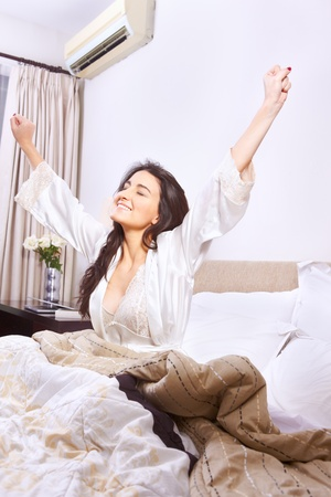 Young woman stretching when wake up in the morning photo