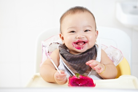 dirty girl: baby girl eating red dragon fruit Stock Photo