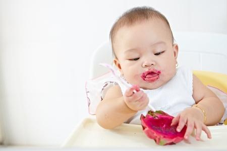 baby girl eating red dragon fruit Standard-Bild