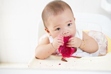 baby eating: baby girl eating red dragon fruit Stock Photo