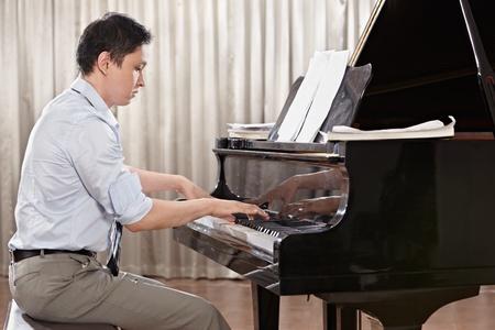 tocando piano: Un joven tocando el piano en el escenario