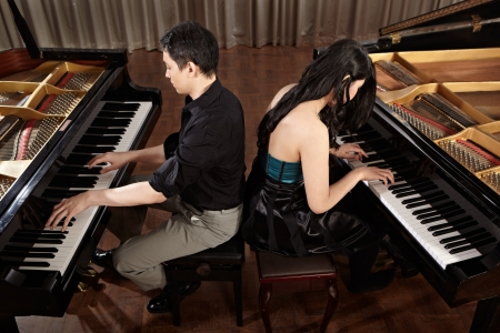 duet: Two people, a couple playing duet musical performance with two grand pianos