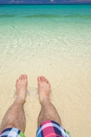 feet relaxing: mans feet relaxing on beach with clean salt water Stock Photo
