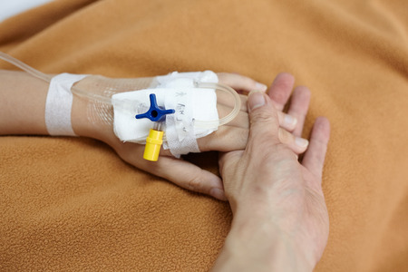 catheters: Hand holding patient hand in the hospital Stock Photo