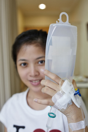 iv: Patient Hold her IV drip tube to go to toilet. Focus on the hand holding the IV tube Stock Photo
