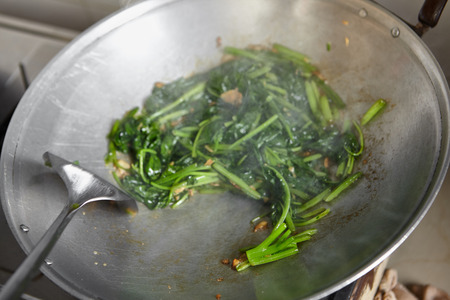 chinese spinach: Sauteing or stir frying the japanese spinach in chinese style Stock Photo