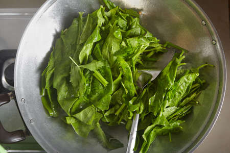 wok: Cooking Japanese spinach or Po Chai on the wok