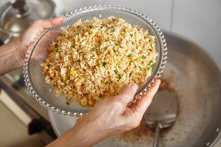 has been: Hand holding a plate with fried rice which has been finished Stock Photo