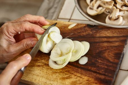 might: Cutting onion on wooden cutting board along another ingredients, slight blur movement might be noticeable