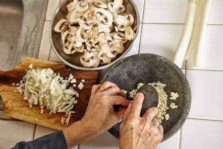 slight: Hand crushing the garlic on mortar, slight movement blur on hand holding pebles to crush it.
