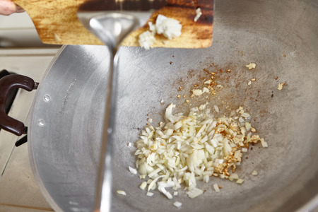 wok: Frying the onion on the wok along with garlic Stock Photo