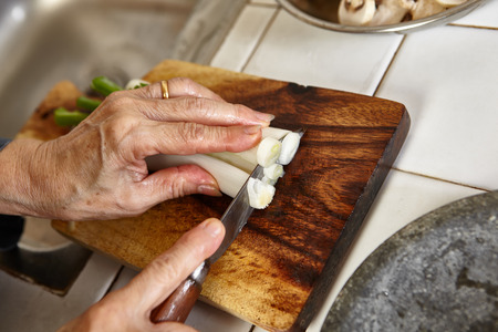 noticeable: Cutting the leek on wooden cutting board, slight movement blur might be noticeable Stock Photo