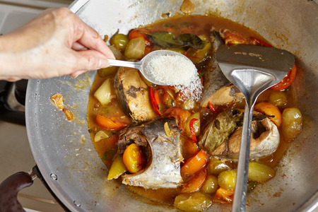 bilimbi: Adding sugar to the cooking on the wok