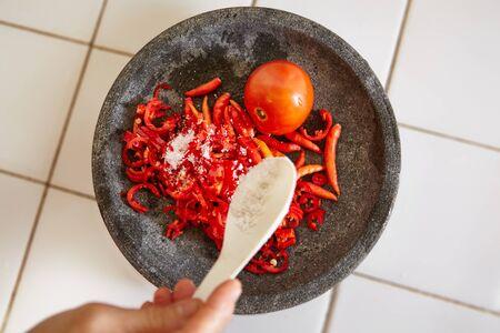 pebles: Adding salt to sambal on stone mortar