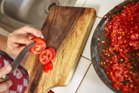 pebles: Cutting tomatoes for additional ingredient for sambal