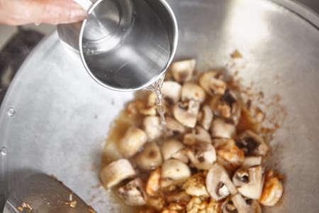 wok: Adding water to the wok Stock Photo