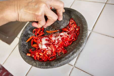 pebles: Crushing chillies with stone mortar and pebles Stock Photo