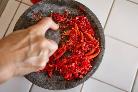 chillies: Crushing chillies with stone mortar and pebles Stock Photo