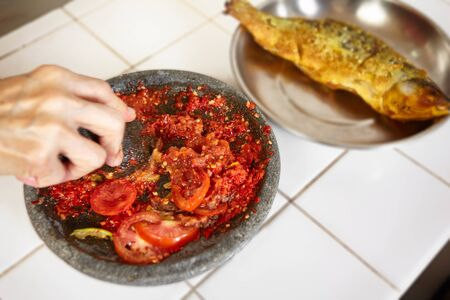 pebles: Crushing chillies with stone mortar and pebles with fired fish on the background