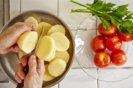 slice tomato: Cutting potato in big slice. Tomato and parsley on background
