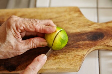 cutting: Cutting lime on the wooden cutting board Stock Photo