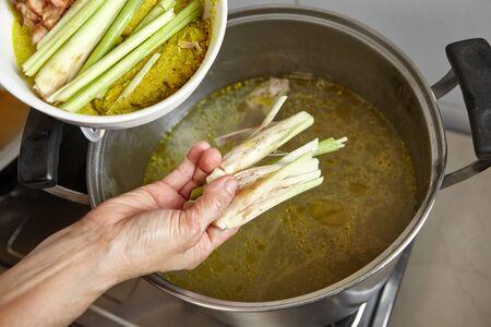 sopa de pollo: Adición de especias y hierbas a la sopa de caldo de pollo Foto de archivo
