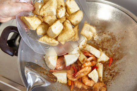 spicy cooking: Adding soft tofu to the cooking on the wok