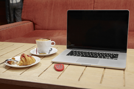 Laptop; e banking token; croissant and coffe on cafes table Stock Photo