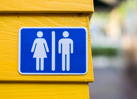 Toilet sign on wall yellow background photo