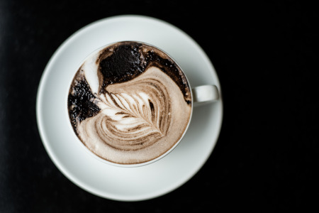 Cup of coffee over the black background photo