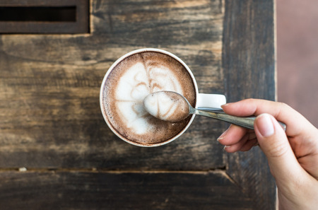 Womans hands holding a spoon with a cup of cofee on top view