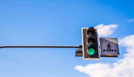 green traffic light in front of blue sky and walk sign photo