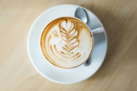 A cup of coffee in a white cup on wooden background photo