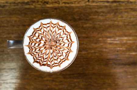 Een kopje koffie in een witte kop op houten achtergrond